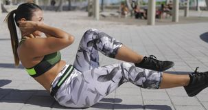 Woman exercising abs on pavement stock footage