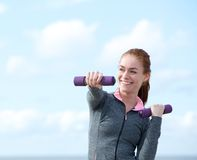 Woman exercising with aerobic weights outdoors Stock Images