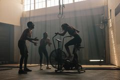 Friends motivating woman on exercise bike in gym. Woman exercising on air bike at gym with friends motivating. Female using air bike for workout at cross Royalty Free Stock Photos