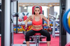 Woman exercising arms gym machine Royalty Free Stock Photo