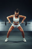 Woman exercising with barbell and weights Stock Images