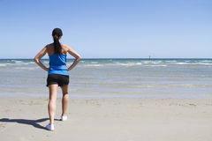 Woman exercising on a beach. Woman exercising on the beach facing the sea Royalty Free Stock Image