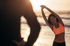 Woman exercising at the beach with her trainer. Woman in sportswear exercising at the beach with her trainer. Athletic woman working out at the beach in morning Royalty Free Stock Images