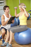 Woman Exercising Being Encouraged By Personal Trainer In Gym Stock Photo
