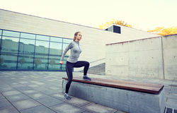 Woman exercising on bench outdoors Stock Photo