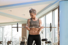 Woman Exercising Biceps With Barbell In Gym Stock Image