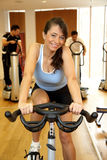 Woman on exercising bike smiling Royalty Free Stock Image