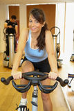 Woman on exercising bike smiling Stock Photo