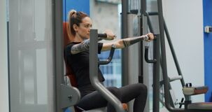 Woman exercising at chest press machine.Woman training at gym machine.Side view, medium shot.Woman pressing bars doing