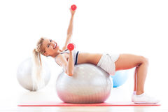 Woman exercising with dumbbells on a fitness ball Stock Images