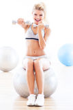 Woman exercising with dumbbells on a fitness ball royalty free stock image