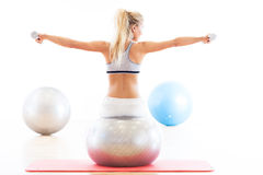 Woman exercising with dumbbells on a fitness ball Royalty Free Stock Photo