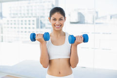 Woman exercising with dumbbells in fitness studio Stock Images