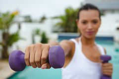 Woman exercising with dumbbells near swimming pool in the backyard. Close-up of mixed-race woman exercising with dumbbells near swimming pool in the backyard stock images