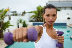 Woman exercising with dumbbells near swimming pool in the backyard. Front view of fit mixed-race woman exercising with dumbbells near swimming pool in the stock photography