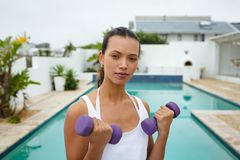 Woman exercising with dumbbells near swimming pool in the backyard. Portrait of beautiful fit mixed-race woman exercising with dumbbells near swimming pool in stock images
