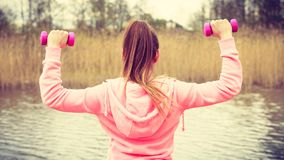Woman exercising with dumbbells outdoor Royalty Free Stock Image