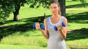 Woman exercising  with dumbbells outdoors Royalty Free Stock Photos
