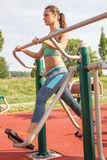 Woman exercising with  elliptic bike in public park on sunny da. Young woman exercising with exercise equipment in the public park Stock Photos