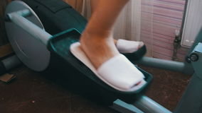 Woman Exercising on the Elliptical Trainer Cross Trainer at Home. Sport woman is engaged in sports at home. Girl on the Elliptical Trainer. Home fitness stock footage