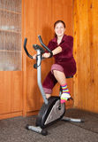 Woman  exercising on exercise bike Stock Image