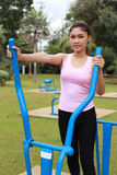 Woman exercising with exercise equipment in the pa Stock Photos