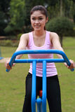 Woman exercising with exercise equipment in the park Royalty Free Stock Image