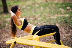 Woman exercising with exercise equipment in the public park. Woman in a sports simulator training on the playground outdoors stock image