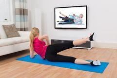 Woman Exercising On Exercise Mat In Front Of Television Stock Images