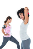 Woman exercising while female friend stretching Royalty Free Stock Image