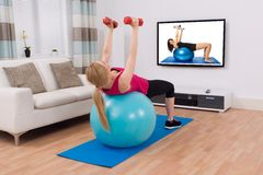 Woman Exercising With Fitness Ball And Dumbbell Royalty Free Stock Photography