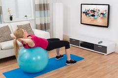 Woman Exercising With Fitness Ball While Watching Program Royalty Free Stock Photos