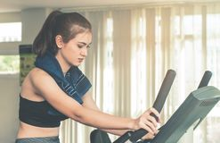 Woman is exercising on a fitness machine Stock Photos