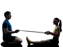 Woman exercising fitness resistance  rubber band with man coach. One women exercising resistance rubber band fitness workout with men coach in silhouette on Royalty Free Stock Images