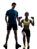Woman exercising fitness weight training with man coach silhouet. One women exercising fitness weight training with men coach in silhouette on white background Royalty Free Stock Image