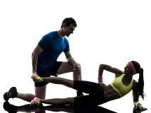 Woman exercising fitness workout with man coach silhouette Royalty Free Stock Photography