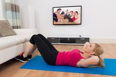 Woman Exercising In Front Of Television Stock Image