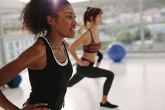 Woman exercising in gym class. African young women exercising in gym class. Stretching workout session in health center Royalty Free Stock Images