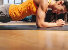 Woman exercising in the gym. Cropped shot of woman exercising in the gym. Muscular female doing core workout on fitness mat with copy space Royalty Free Stock Photo
