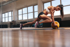 Woman exercising in the gym. Cropped shot of woman exercising in the gym. Muscular female doing core workout on fitness mat with copy space Royalty Free Stock Images