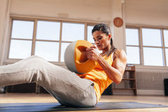 Woman exercising in the gym. Cropped shot of woman exercising in the gym. Muscular female doing core workout on fitness mat with copy space Royalty Free Stock Image