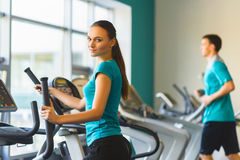 Woman exercising at the gym on a cross trainer Stock Photo