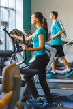Woman exercising at the gym on a cross trainer Stock Image
