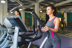 Woman exercising at the gym on a cross trainer Stock Images