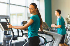 Woman exercising at the gym on a cross trainer Royalty Free Stock Photos