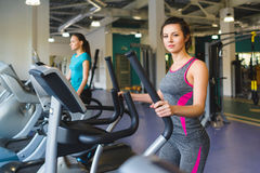 Woman exercising at the gym on a cross trainer Stock Photos