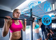 Woman exercising in gym. Digital composition of woman exercising in gym and fitness interface Royalty Free Stock Photo