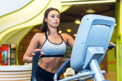 Woman exercising at the gym in an elliptical trainer Cardio training. Royalty Free Stock Images