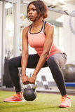 Woman exercising in a gym with a kettlebell weight, vertical Royalty Free Stock Photos