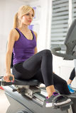 Woman exercising at the gym on a machine Royalty Free Stock Images